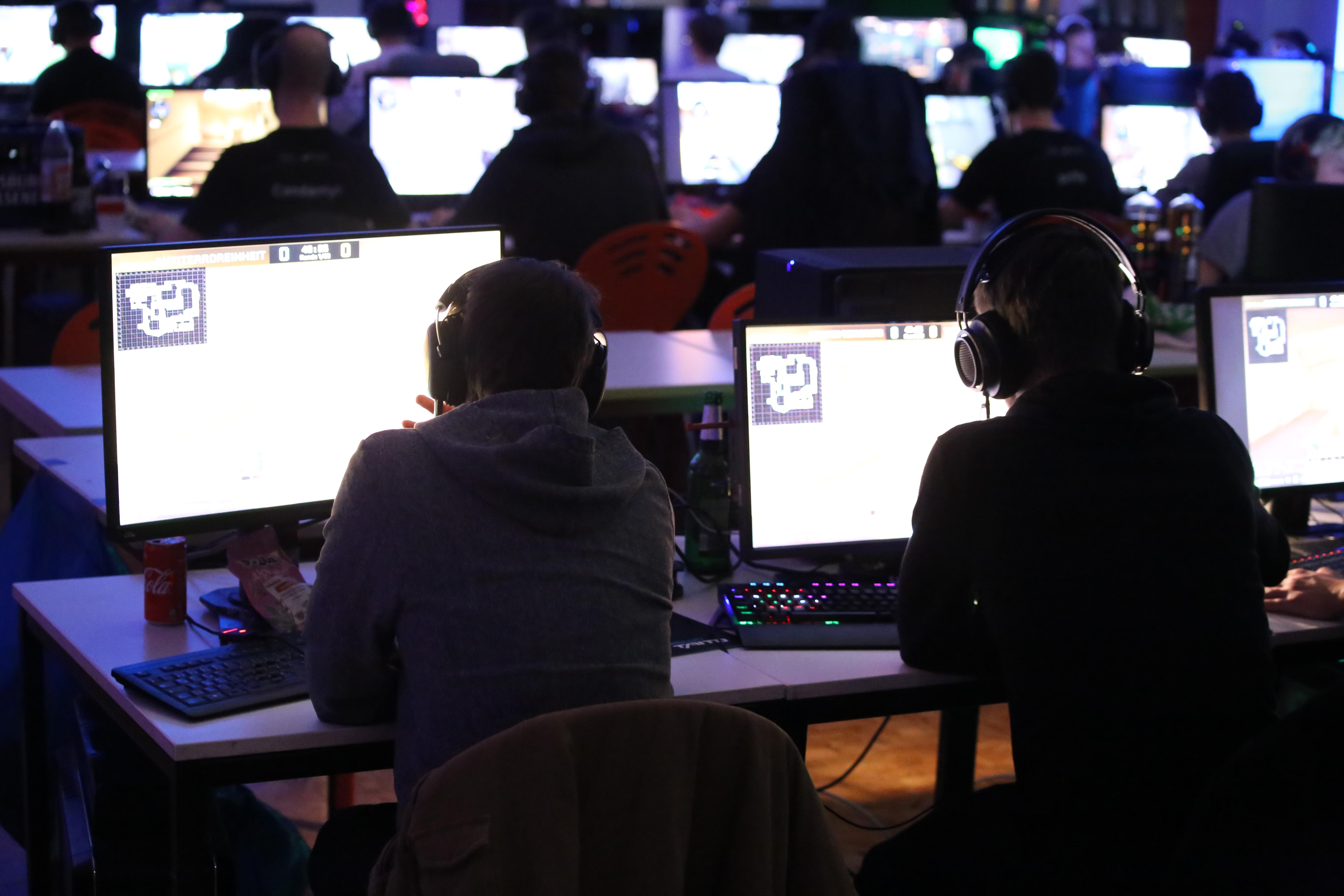 SX23- Zwei Spieler schauen auf ihre Monitore